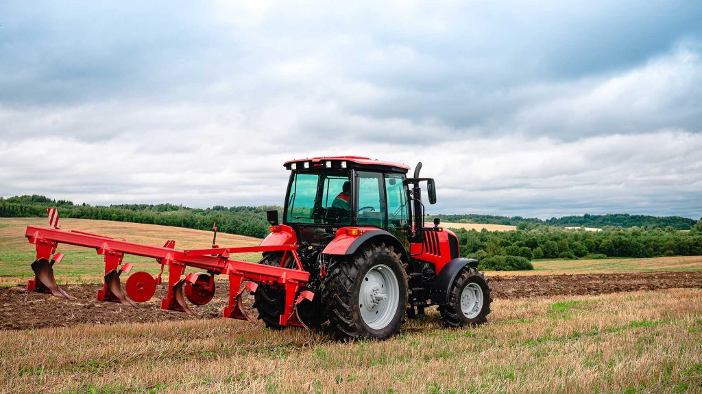 EMT Tractor with plow, Small scale farming with tractor and plow in field. Heavy agricultural machinery for field work