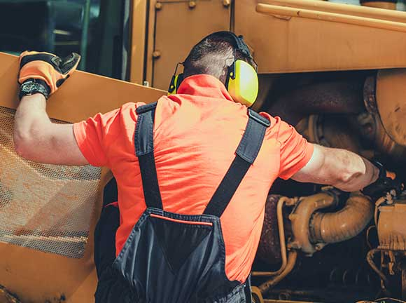 equipment technician applying fixes on heavy equipment
